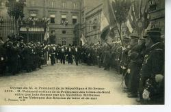 Voyage de Monsieur le Président de la république M. Poincaré à St Brieuc. M. Poincaré sortant de la préfecture des Côtes du Nord entre une haie formée par les médaillés et les vétérans des armées de terre et de mer  | Poincaré, Raymond